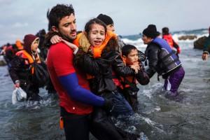Un bagnino di salvataggio volontario aiuta una bambina dopo l'urto della barca che trasportava la sua famiglia con altri rifugiati afghani contro gli scogli dell'isola di Lesbo