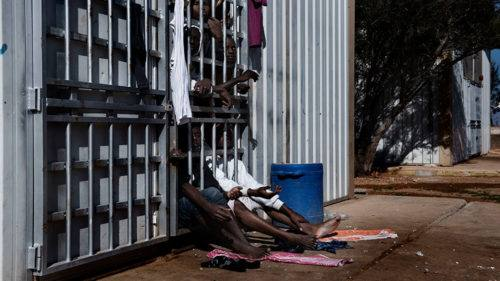 """Migrants look out from behind the bars of a cell at the detention centre in Garian, Libya, Tuesday 31 January 2017. The Garian detention centre, located 70 kilometres south of Tripoli, was constructed in 2006 following an agreement between the Italian and Libyan governments in an attempt to stem the flow of migrants reaching Italy. When UNICEF visited the centre on 31 January 2017, the population consisted of 27 women (four of whom were pregnant), one 11-month old child, a four year old, as well as 1,352 men - of which 250 were under the age of 16. The centre is at the crossroads of areas controlled by different militias fighting with each other: the Warshafana, the militias of Tripoli and the militias who support Haftar in Benghazi. For this reason it is a very dangerous centre, for officers who work there and for migrants in detention. The detention centre is currently managed by the Libyan National Army, and most migrants remain there for a period of 8 to 10 months according to the manager Abdalhamad Altunisa. """"Children are often alone, they cross 2000 kilometres of desert without their families, and they are rescued at sea without documentsî, said Altunisia ìthis makes it difficult for us to know their real nationality and age. Before 2014 we brought them back to the border between Nigeria and Libya to take them back to their countries, but after the last civil war it was much more difficult. Those areas are dangerous even for usî. Migrants who were being held in the cells said they are rarely allowed out. Many of the those being held are sick, and some detainees are said to have passed away because they have no access to medical care. The director of the centre, Altunisa, said """"the official government [of Sarraj] does not give us the money to pay salaries and to pay those who bring us food. So often we do not have enough food or drinking water. This winter was particularly cold and in recent weeks 15 migrants froze to death."""" Libya is a country in turm"""